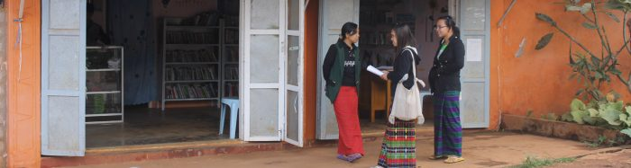 Three women stand outside a library in Myanmar
